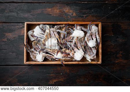 Frozen Raw Blue Swimming Crab Claws Set, In Wooden Box, On Dark Wooden Background, Top View Flat Lay