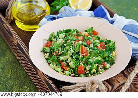 Tabbouleh, Parsley, Tomato And Cucumber Vegetable Salad With Bulgur In A Clay Plate On An Olive Conc