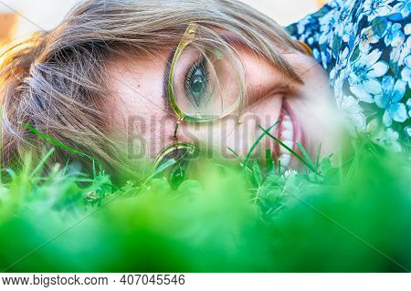 Portrait Of A Woman Sitting In The Grass. Hdr Image.