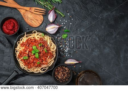 Italian Dish Pasta Bolognese With Basil Surrounded By And Onions On A Black Background.