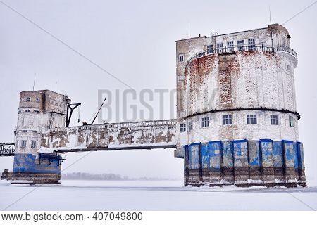 An Old Water Intake Station On A Frozen River Covered In Snow And Ice. Abandoned Landscape