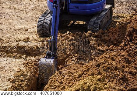 Digging A Trench For The Foundation. Ground In Backhoe Dump Bucket For Earthmoving Works In Construc