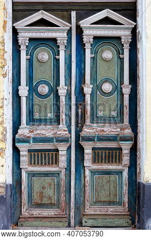 Old High Wooden Entrance Doors In White, Blue And Green With Carved Elements Frame The Entrance Of T