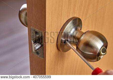 Locksmith Fixes Door Handle Rose With Screw, Using  Screwdriver.