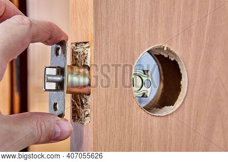 Locksmith Pushes Latch Assembly Through Hole On New Door During Installation.