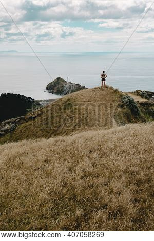 Woman Conquering The Top Of Castle Rock Mountain And Looking At Castle Point Lighthouse. New Zealand