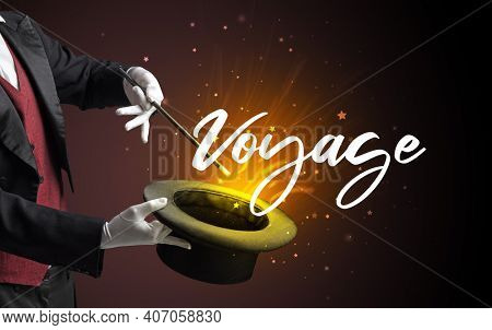 Magician is showing magic trick with Voyage inscription, traveling concept