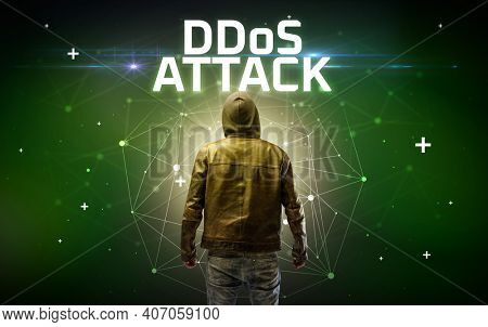 Mysterious hacker with DDoS ATTACK inscription, online attack concept inscription, online security concept