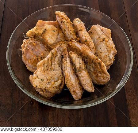 Chicken Buffalo Wings Raw In Bowl With Garlic Parmesan Sauce Flavored On An Isolated Background.