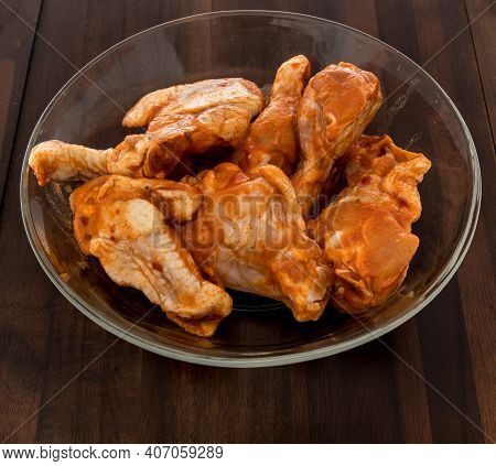 Chicken Buffalo Wings Raw In Bowl With Spicy Sauce Flavored On An Isolated Background.