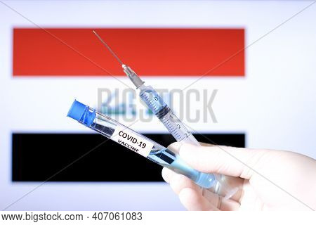 Hand In Surgery Glove Holding Syringe With Covid Vaccine. Iraqi Flag In The Background