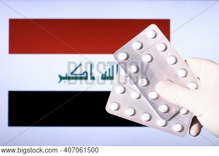 Hand In Surgical Glove Holding Pill Blisters. Iraqi Flag In The Background