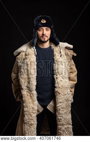 Portrait Of A Confident Man Of Caucasian Appearance In A Soviet Officer Fur Hat And Army Sheepskin C