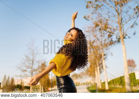 The Girl Threw Her Hands Up, Rejoices, Celebrates And Dances In The Autumn Park. High Quality Photo
