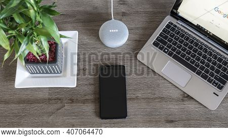 Adelaide, Australia - July 7, 2019: Google Home Mini With Hp Laptop Running Windows 10 And Mobile Ph