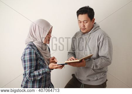 Asian Young Muslim Couple Checking Analyzing Their Family Financial Management Report, Young Family