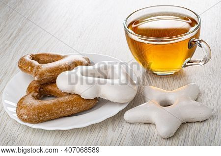 Brown And White Gingerbreads Different Shape In Plate, Transparent Cup With Tea, Gingerbread In Shap