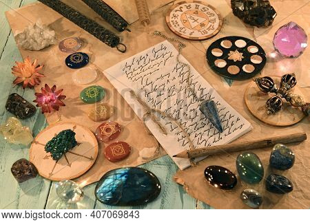 Crystal Stones With Chakras, Candles, Ritual Objects And Paper With Lettering And Text On The Table.