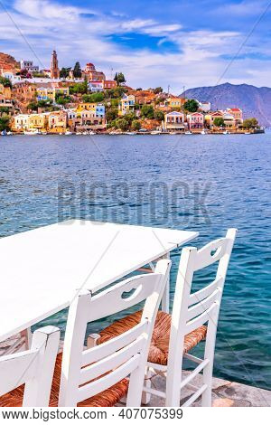 Symi, Greece. Typical Greek Tavern White Chairs With Tables, Sea In Rhodes.