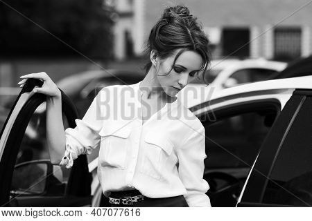 Young fashion business woman next to her car  Stylish female model with bun up do hair in white shirt