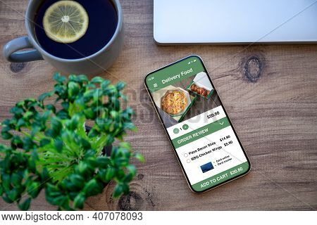 Phone With Food Delivery App On Wooden Table In Office