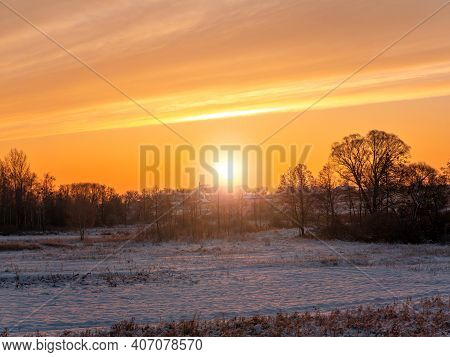 Sunny Sunset Over A Snowy Agricultural Field In Winter. Sunrise. White Snow. Cloudy Horizon. Sun Ray