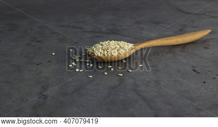 A Spoon Of White Sesame On Black Background