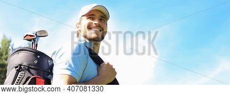Portrait Of Male Golfer Carrying Golf Bag While Walking By Green Grass Of Golf Club.