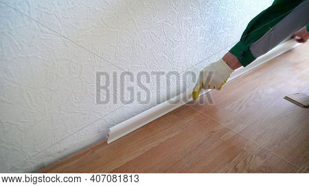 Newly Renovated And White Skirting Boards In The Apartment. Primed White Wall And Wooden Parquet Flo