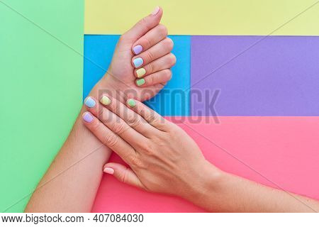 Female Hands With Bright Summer Nails On A Colorful Background. Top View