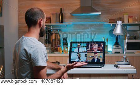 Employee Working Remotely Discussing With Partners Online Using Laptop Sitting In The Kitchen. Freel