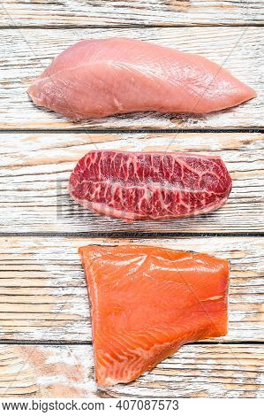 Three Types Of Steaks On Wooden Table. Beef Top Blade, Salmon Fillet And Turkey Breast. Organic Fish
