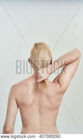 Rear View Of Shirtless Young Caucasian Man Holding His Long Blond Hair In Hand While Standing On Whi