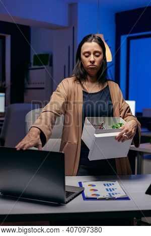 Depressed Employee After Being Fired With Cardbox In Hands. Sad Woman Holding Her Belongings Late At