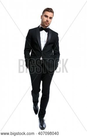 full body picture of elegant young man in black tuxedo holding hands in pockets and walking isolated on white background in studio