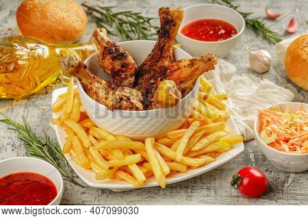 Closeup Of A Portion Of Grilled, Roasted Chicken Legs With Golden Brown Crust, Served On A White Pla