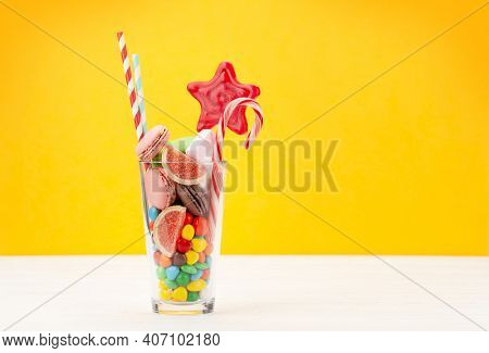 Various sweets assortment. Candy, bonbon, chocolate and macaroons in cocktail glass over yellow background. With copy space