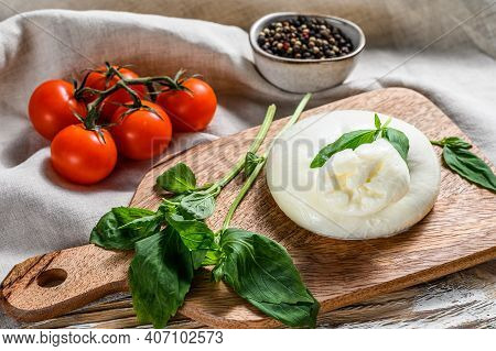 Italian Burrata Buffalo Cheese With Basil Leaves. White Wooden Background. Top View
