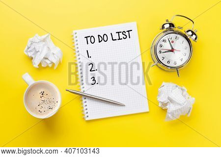 Office desk with coffee, alarm clock and notepad with to do list over yellow. Creativity and inspiration work concept. Top view flat lay with copy space