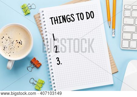 Business desk workplace with to do list notepad and office objects over blue backdrop. Top view flat lay