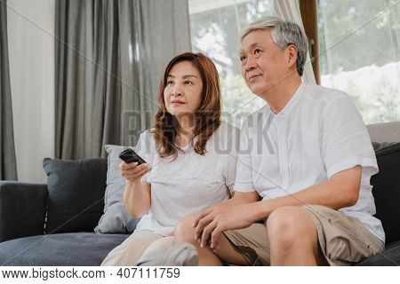 Asian Elderly Couple Watching Television In Living Room At Home, Sweet Couple Enjoy Love Moment Whil