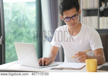 Asian Young Student Man Entrepreneur Working With Computer Studying Learning Online At Home. E-learn