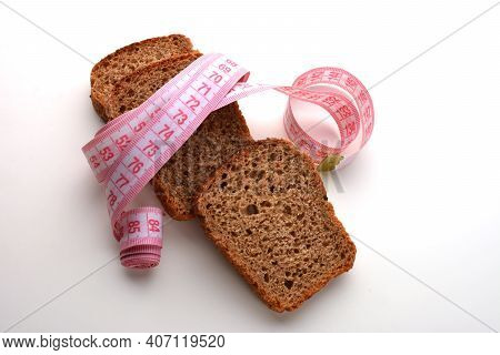 Diet Concept - Piece Of Bread Grasped By Measuring Tape Isolated On White.