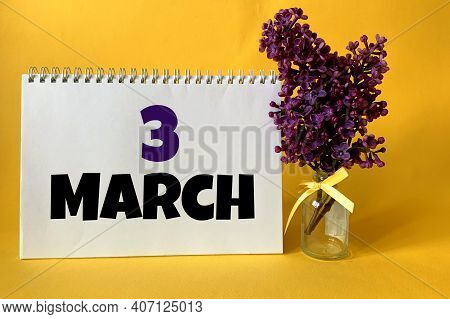 March 3 On A White Notebook On A Yellow Background.next To It Is A Sprig Of Lilac .calendar For Marc