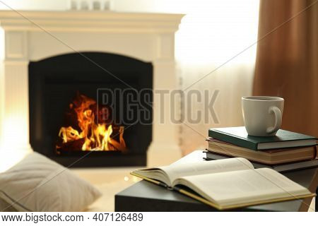 Cup Of Hot Drink And Book On Table Near Fireplace At Home. Cozy Atmosphere