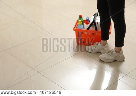 Woman And Shopping Basket With Household Goods On Ceramic Floor, Closeup. Space For Text