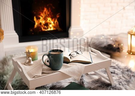 Cup Of Coffee, Burning Candle And Book On Tray Near Fireplace Indoors. Cozy Atmosphere