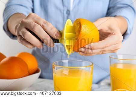 Woman Squeezing Orange Juice At Table, Closeup