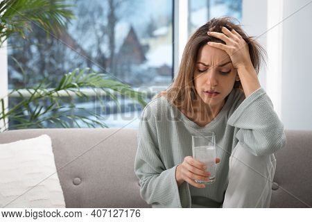 Woman Holding Glass Of Medicine For Hangover At Home