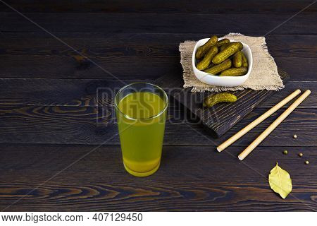 Cucumber Pickle Or Pickle Juice In Glass, A Bowl With Pickled Gherkins On A Wooden Background. Trend
